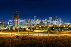Long Exposure of Denver City Skyline during night with green gra. Ss and light trails Royalty Free Stock Images