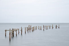 Long exposure derelict pier in calm sea Royalty Free Stock Photo