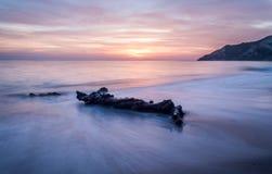 Long exposure of driftwood amazing sunset colors. In Corfu Greece Ionian Islands Europe Stock Photo