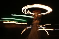 Long exposure fire show. Long exposure image of an art performer at a fire show in the dark stock images