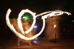Long exposure fire show. Long exposure image of an art performers at a fire show in the dark royalty free stock images