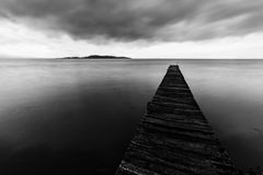 Long exposure first person view of a pier on a lake, with perfectly still water. Long exposure first person view of a pier on a lake with perfectly still water Stock Photo