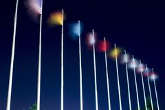 Long exposure flags. Waving flags on the wind at night. Different countries flags are on the pillars stock photos