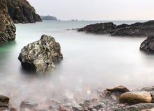 Long exposure flowing tide over rocks Stock Image