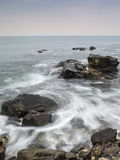 Long exposure flowing tide over rocks Stock Photo