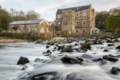 Long exposure shot of Hirst Weir, Yorkshire. Long exposure gives the water a silky look as it flows over the weir in front of historic Hirst Mill stock photo