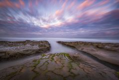 Long exposure of high tide water in La Jolla California at sunrise. Colorful sunrise over a tide pool area in La Jolla California royalty free stock images