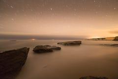 Long exposure image of coastal rocks on ocean beach Stock Photos