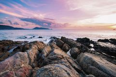 Long exposure image of Dramatic sky seascape with rock in sunset Royalty Free Stock Image