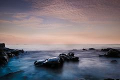 Long exposure image of Dramatic sky and wave with rock sea in sunset scenery background. Long exposure image of Dramatic sky and wave with rock sea in sunset stock photos
