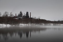 Long exposure image of industrial plant near pond with steam on Stock Photo