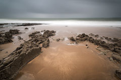 Long exposure landscape beach scene with moody sky Stock Image