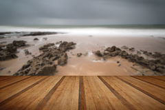 Long exposure landscape beach scene with moody sky with wooden p Stock Image