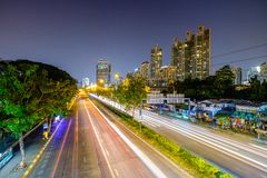 Long exposure landscape of city and traffic lights trail in Bang. Kok, Thailand, South East Asia. A man is blurred due to the long exposure Royalty Free Stock Photography