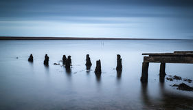 Long exposure landscape of old derelict jetty extending into lak Stock Images