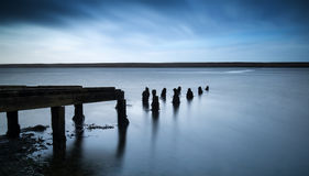 Long exposure landscape of old derelict jetty extending into lak Royalty Free Stock Photos