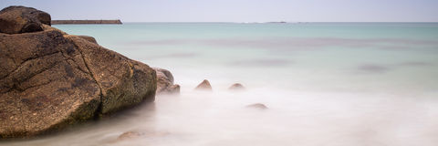 Long exposure landscape panorama of rocks on beach at low tide Stock Image