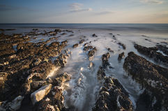 Long exposure landscape rocky shoreline at sunset Stock Photos