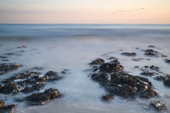 Long exposure landscape rocky shoreline at sunset Stock Photo