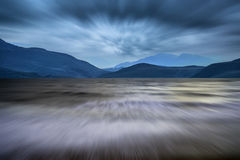 Long exposure landscape of stormy sky and mountains  over lake Stock Images