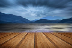 Long exposure landscape of stormy sky and mountains  over lake w Stock Image