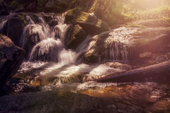 Long exposure at a little waterfall. With sun Stock Image