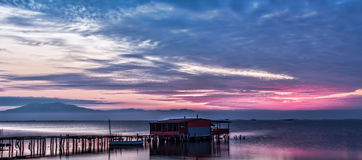 Long exposure of magic sunrise over the ocean with a hut in the. Middle and a wooden bridge Stock Photos