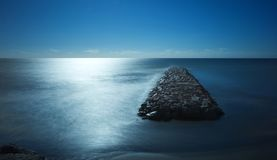 Long exposure, dreamlike view of causeway, cut off by the tide, Torrox Costa, Spain. Royalty Free Stock Image