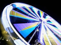 Long exposure motion blur of a spinning ferris wheel at night illuminated in bright neon colors. A long exposure motion blur of a spinning ferris wheel at night stock photography
