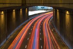 Light trails on a motorway. Long exposure of a motorway traffic at night - light trails painted in the shot with a subway station in the background royalty free stock images