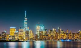Long exposure of New York City Skyline with dark blue sky. Bright yellow city lights and reflections in the river Stock Photography