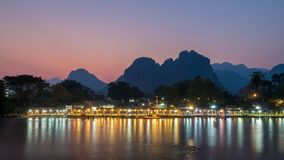 Nightlife along Nam Song River, Laos. Long exposure of night lights of the bars along Nam Song River in Vang Vieng. Red receding light from sun visible in the stock images