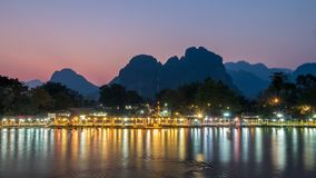 Nightlife along Nam Song River, Laos. Long exposure of night lights of the bars along Nam Song River in Vang Vieng. Red receding light from sun visible in the stock photo