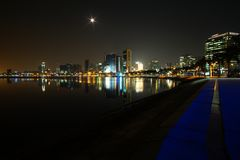 Long exposure night wide angle view of Marginal de Luanda with full moon and Mars moments after the beginning of lunar eclipse stock images