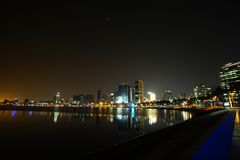 Long exposure night wide angle view of Marginal de Luanda with full moon and Mars during total lunar eclipse stock photo
