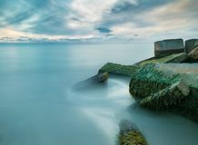 Long exposure of ocean with concrete pillars royalty free stock photography