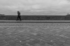 Long exposure of a pedestrian walking on a bridge on a rainy day royalty free stock photography