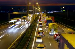 Highway traffic by night. Long exposure photo of highway traffic at night. Lots of trucks and cars on a crowded road in rush hour Royalty Free Stock Photos