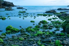 Long exposure photo of a scenic view of rocks covered in moss on a beach south of Taiwan royalty free stock image