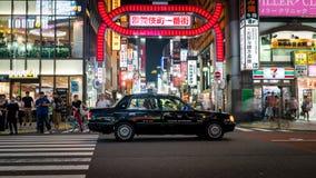 Long exposure photo of a taxi at a crossroads in Kabukicho in the Shinjuku, Tokyo, Japan. Tokyo, Japan - August 2018: Long exposure photo of a taxi at a stock image