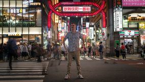 Long exposure photo of a tourist standing at a crossroads in Kabukicho in the Shinjuku, Tokyo, Japan. Tokyo, Japan - August 2018: Long exposure photo of a royalty free stock photography