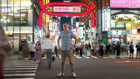 Long exposure photo of a tourist standing at a crossroads in Kabukicho in the Shinjuku, Tokyo, Japan. Tokyo, Japan - August 2018: Long exposure photo of a royalty free stock images