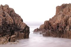 LONG EXPOSURE PHOTOGRAPH ON A BEACH BETWEEN TWO CLIFFS royalty free stock images