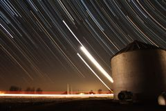 Grains of the Night Sky. A long exposure photograph featuring the Moon and planets Venus and Jupiter. A car's headlight's are seen streaking through during the royalty free stock photo