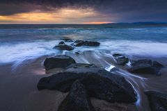 Redondo Beach Sunset. Long-exposure photograph of silky smooth water flowing around rock formations at sunset with dramatic clouds in the sky, Redondo Beach Stock Images