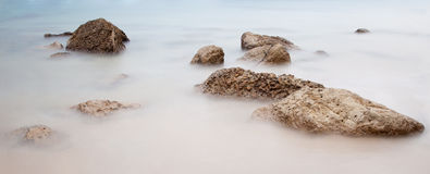 Long exposure photo on a beach full of rocks Royalty Free Stock Image