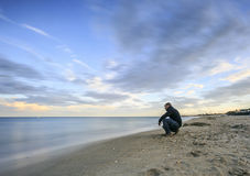 Long exposure photography on  the beach. Man sitting in a Long exposure photography on  the beach Royalty Free Stock Photos