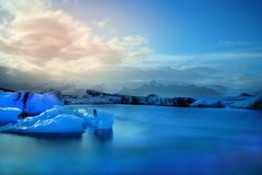 Long Exposure photography of blue iceberg floating in front of snow cap mountain stock image