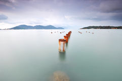 Long exposure of piling pole for unfinished wooden jetty facing Stock Photo