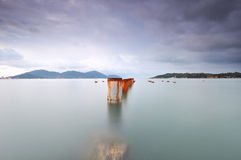 Long exposure of piling pole for unfinished wooden jetty facing Royalty Free Stock Image